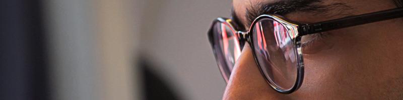 Mann mit Brille sieht sich Seminartermine und Seminaranmeldung an